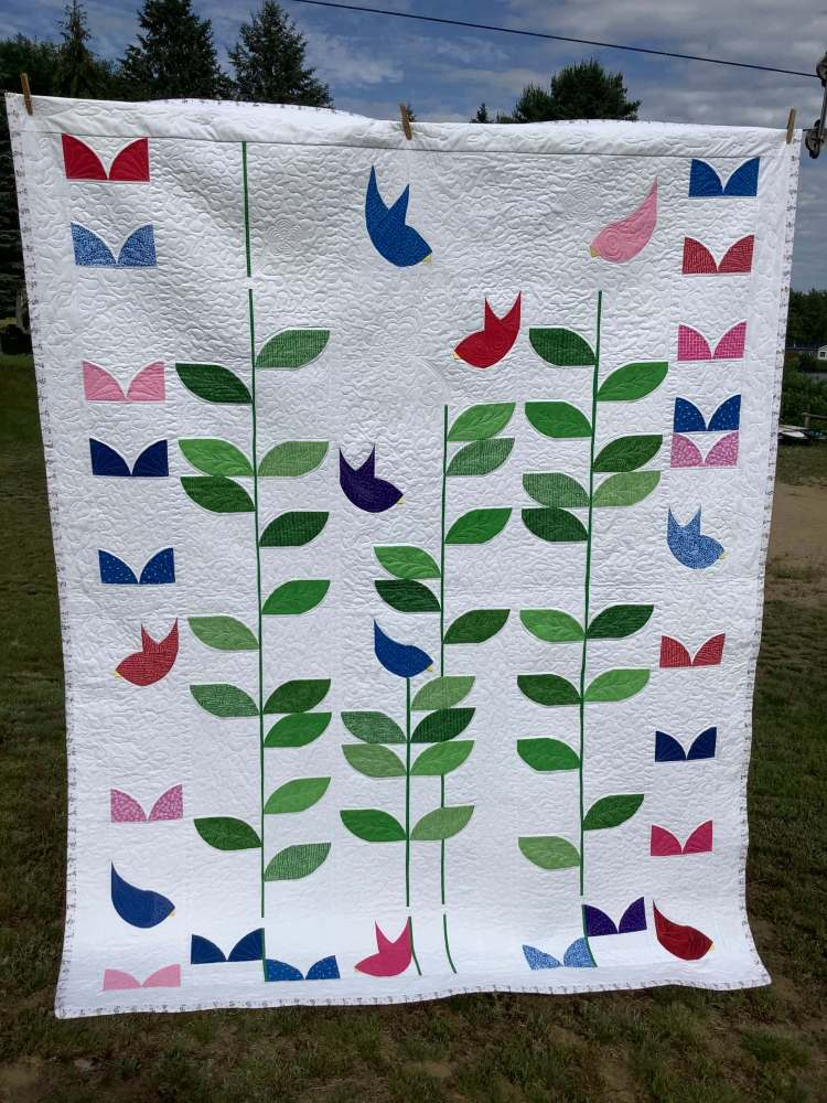 a quilt with bird song pattern by Stich and a Round hanging on a clothline