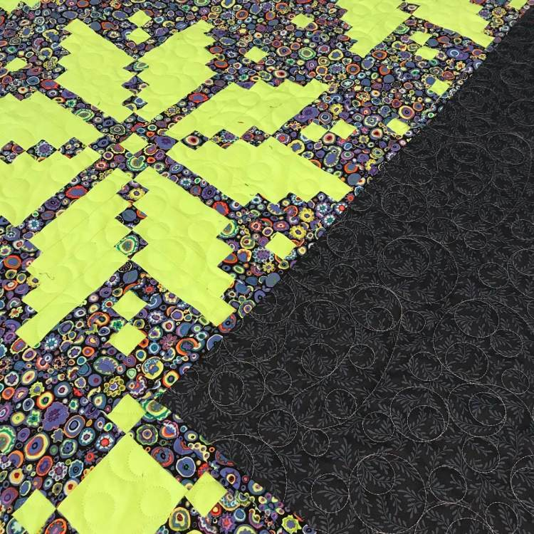a quilt with knitted yellow start/fassett pattern by Stich and a Round