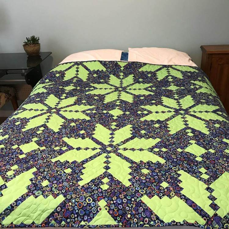 a quilt with knitted start/snowflake pattern placed on a bed by Stich and a Round