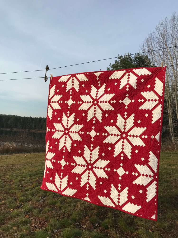 a red quilt with knitted white start/snowflake pattern by Stich and a Round