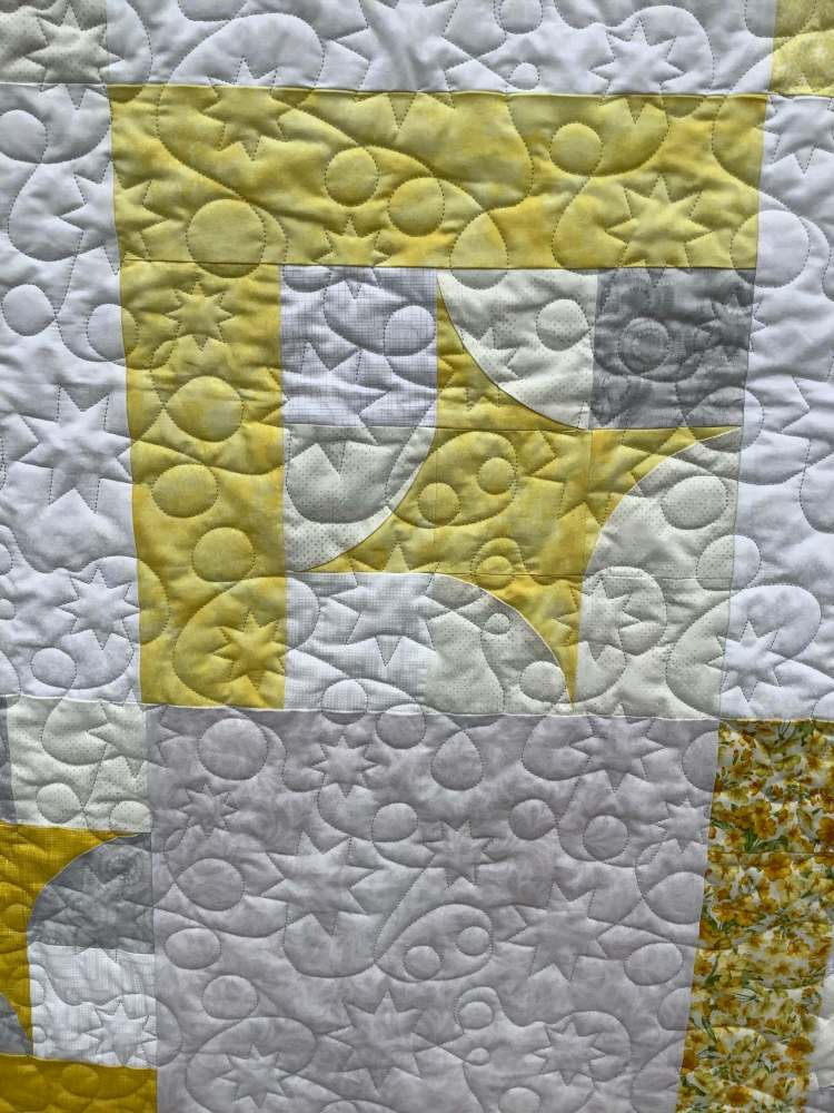 a closeup shot of a quilt with shining star pattern by Stich and a Round