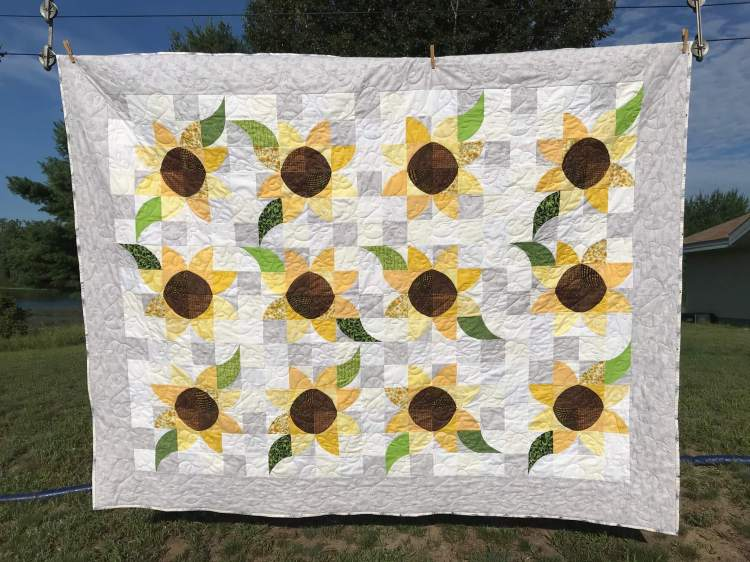 a quilt with soak up the sun pattern by Stich and a Round hanging on a clothline