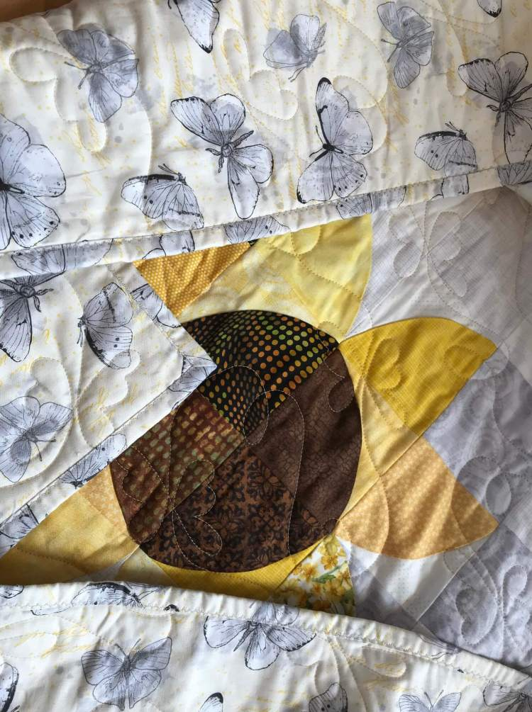 closeup shot of a quilt with soak up the sun pattern by Stich and a Round