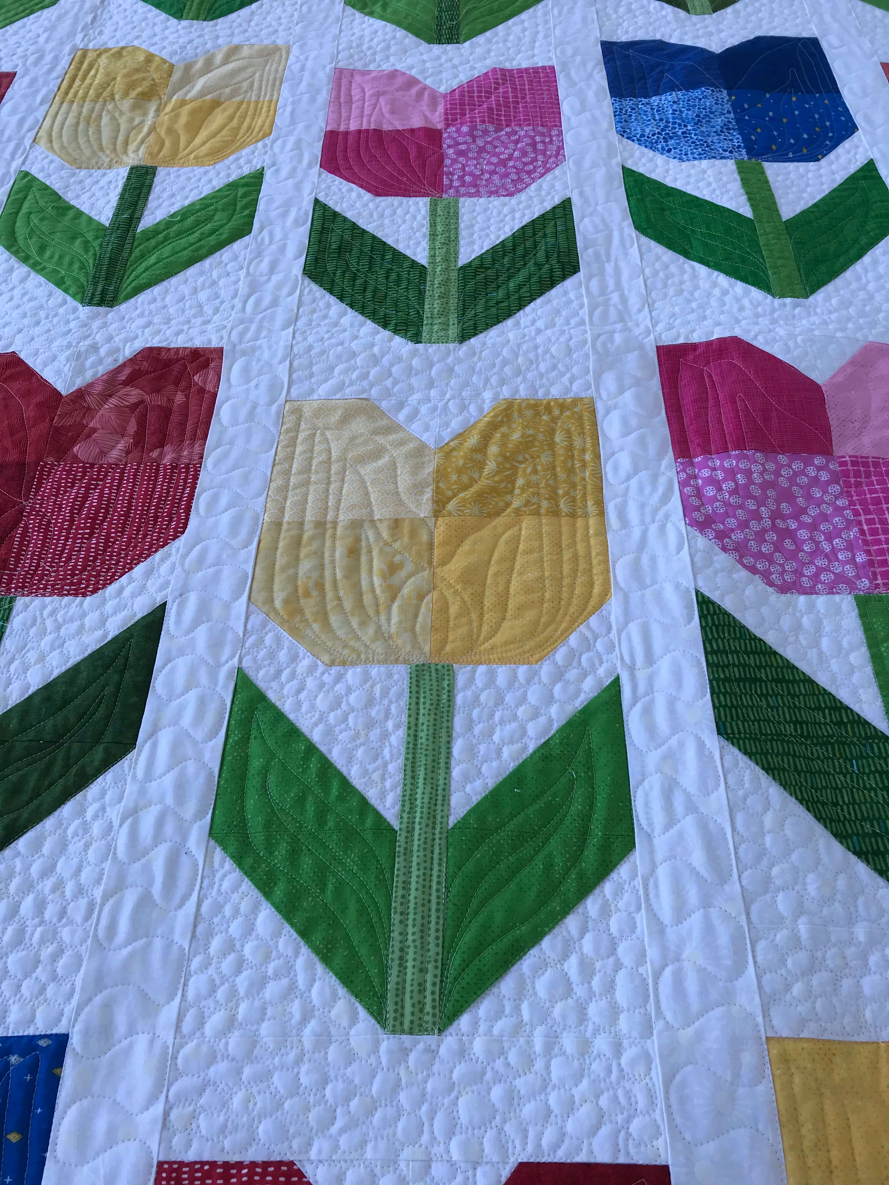 a closeup shot of a quilt with totally tulips pattern by Stich and a Round
