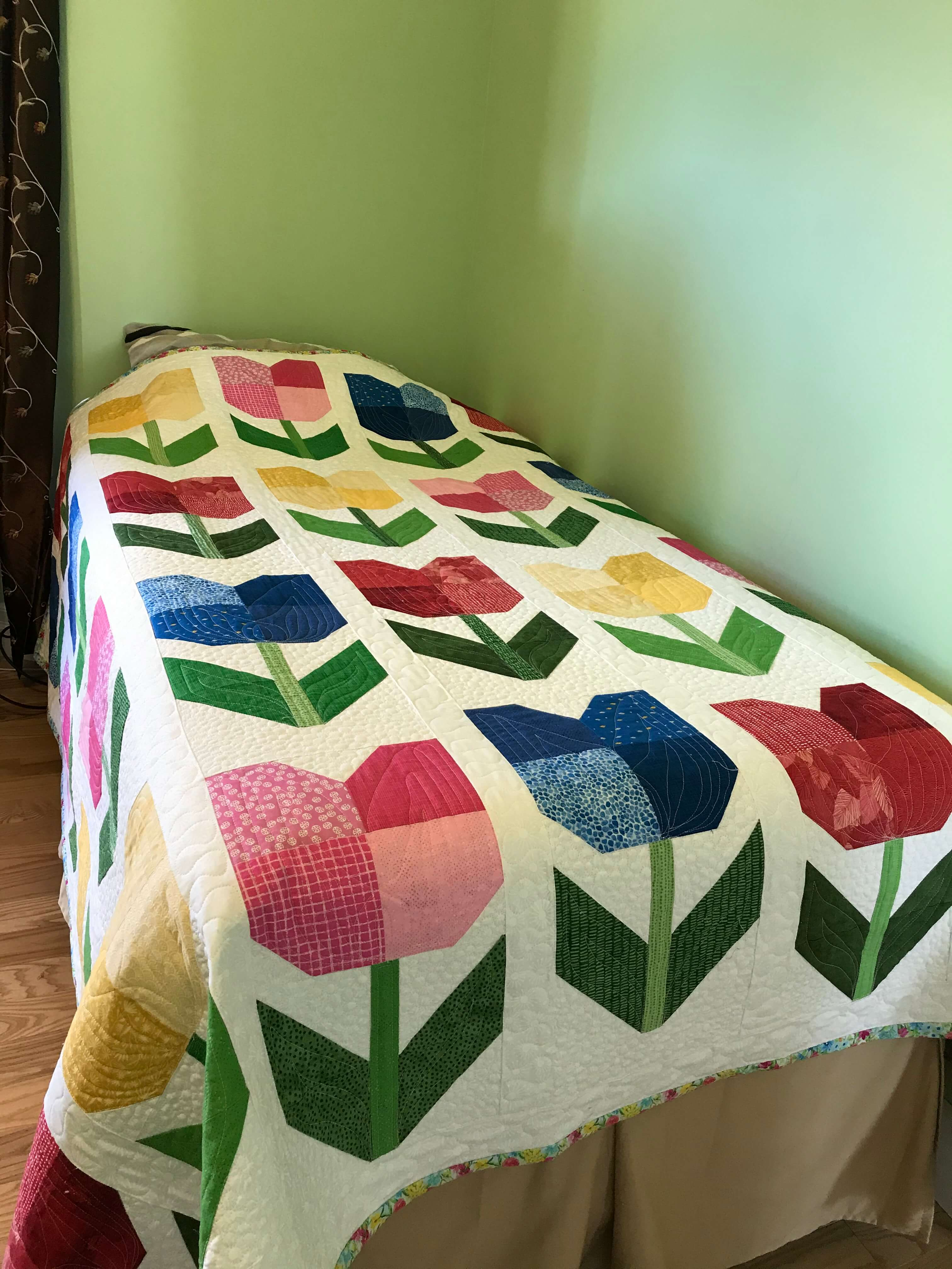 a quilt with totally tulips pattern by Stich and a Round spread over a bed