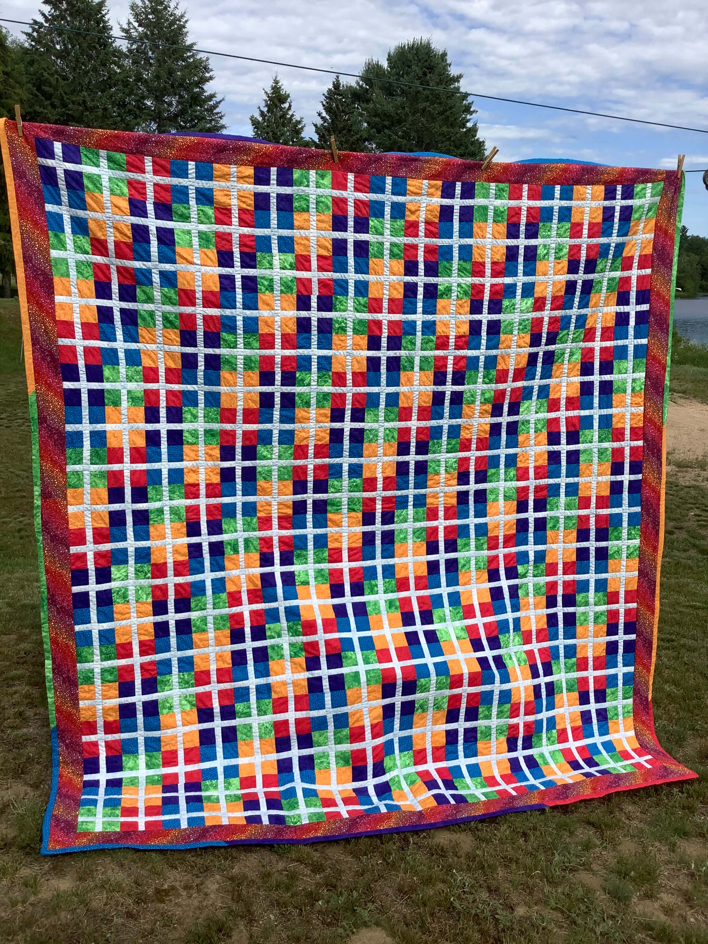 a quilt with young quilt pattern by Stich and a Round hanging on a clothline